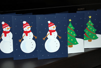 Snowmen army in the forest of Christmas trees. Photo of hand-made Christmas cards.
