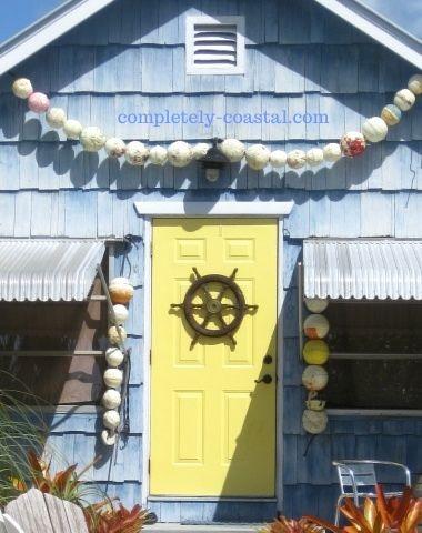 yellow nautical front door decor idea with ship wheel