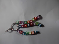 "3-stranded keychain that says ""celebrate autistic culture"" in rainbow letters"