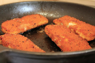 Breaded Tilapia being fried in a skillet