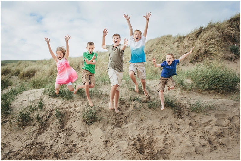 Children jumping off sand dunes on the beach