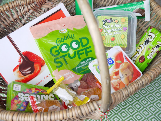 a wicker basket filled with Fry's peppermint cream bars in white and green packaging, a green bag of peach sweets, a red tub of caramel pudding, a green box of fruit shaped jellies, individually wrapped jellies, a box of strawberry cremes with a picture of a strawberry on it, and a green carton of mint chocolate poppets