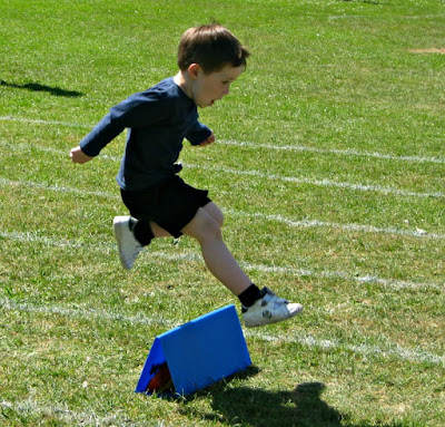 Small boy jumping a hurdle at Sports Day