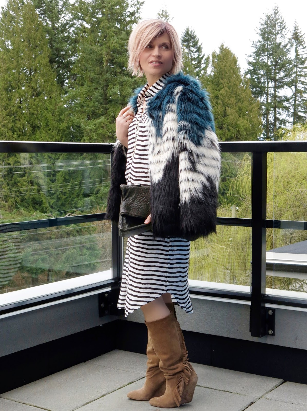styling a striped shirtdress with fringy boots and a colour-blocked, faux-fur jacket