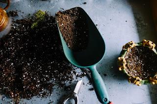 Blue garden spade and black dirt next to a pot. Photo by Neslihan Gunaydin