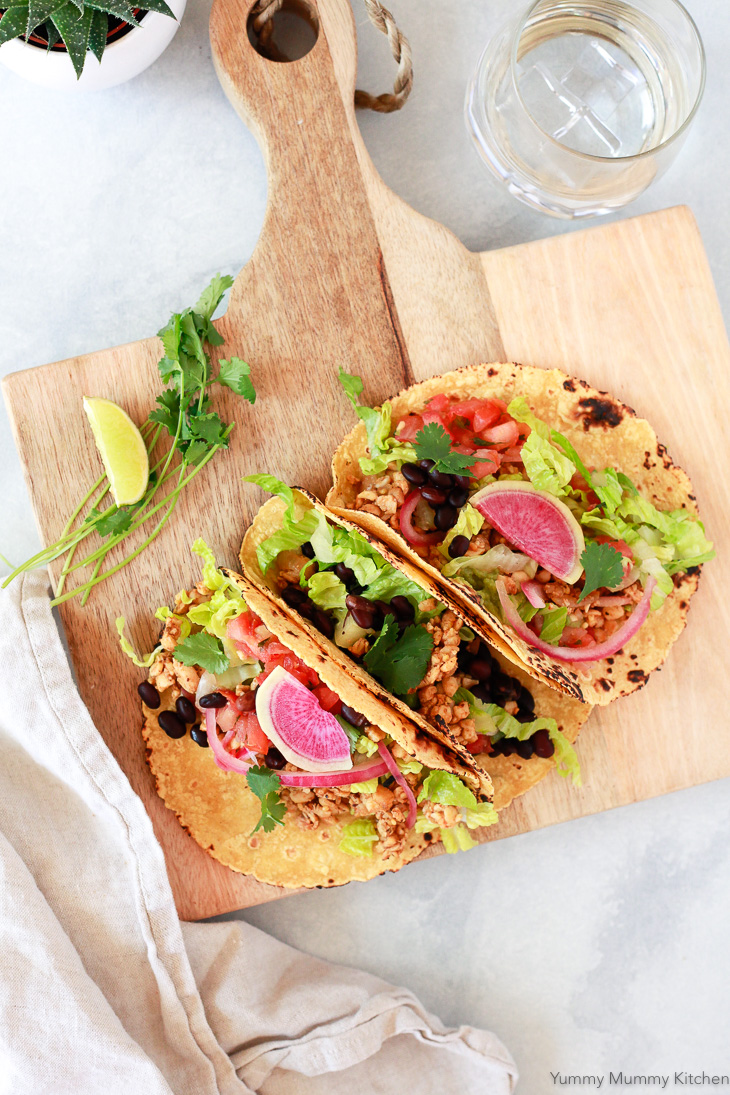 Three colorful vegan tacos with tempeh, black beans, lettuce, and watermelon radish.