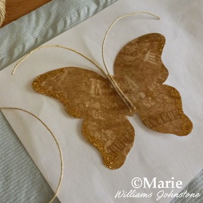 Adding twine antennae to a paper craft butterfly