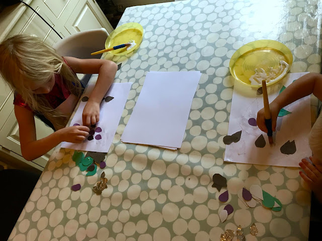 An overhead view of a table with a toddler and 6 year old sticking rainbow shapes to paper