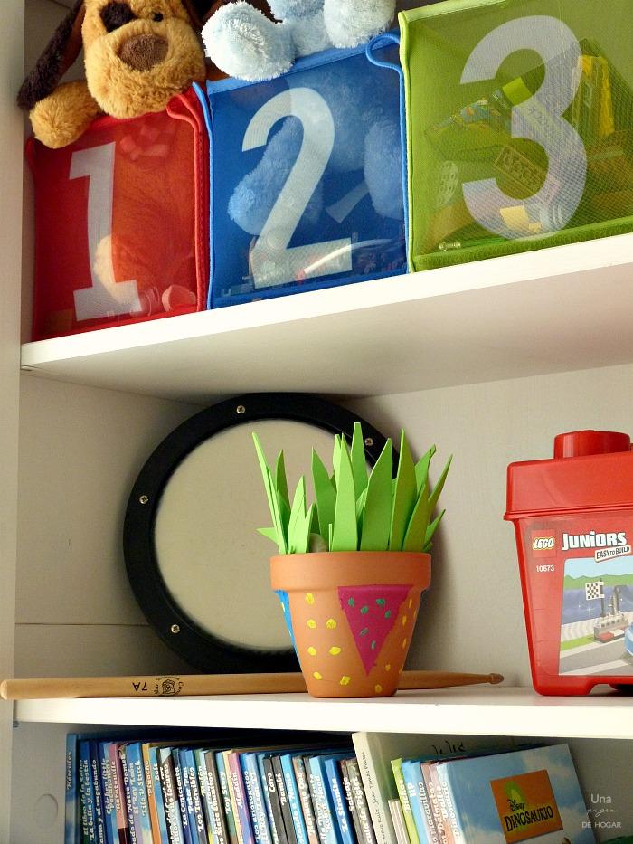 macetas de barro y goma eva decoradas por niños en un dormitorio infantil