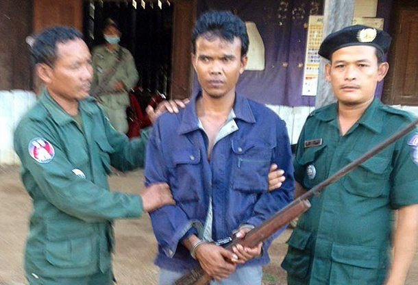A man poses for a photo with a homemade rifle on Tuesday in Preah Vihear after he was arrested for shooting a man in the head with a homemade rifle. Photo supplied