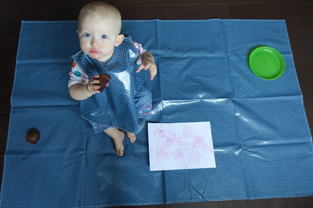 An over head photograph of a baby on a splash mat, wearing a tunic bib and holding a piece of cut beetroot. A white piece of card with pink marks is in front of her