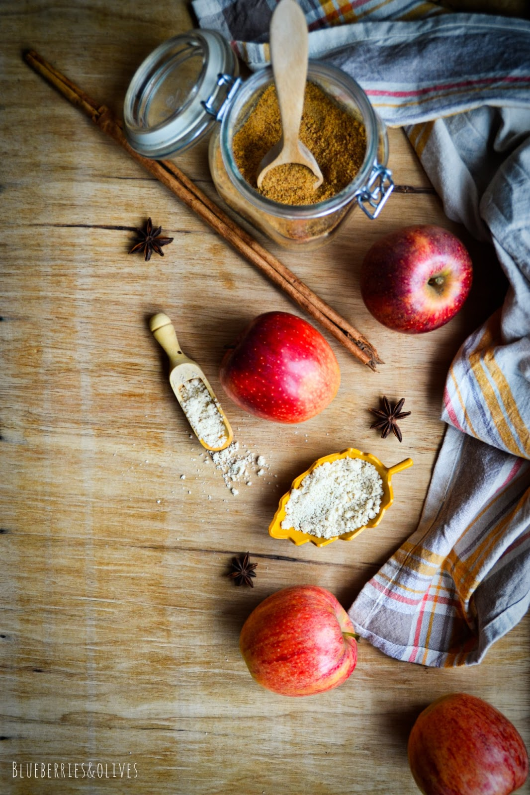 Cooking ingredients on wood table: red apples, brown sugar, star anise, cinnamon sticks