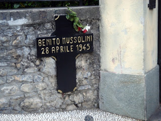 A small cross on a wall in Giulino di Mezzegra marks the spot  at which Mussolini was killed by Tuissa and her comrades