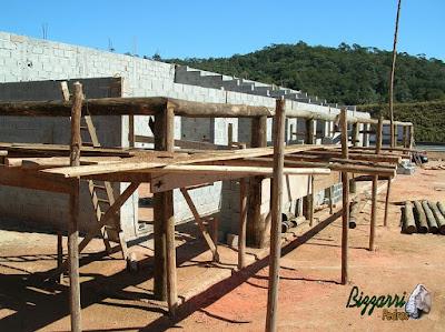 Em cima das muretas de pedra, a colocação dos pilares de madeira com eucalipto tratado de demolição e a colocação dos frechais de madeira onde vão ser apoiadas os caibros de madeira no terraço.