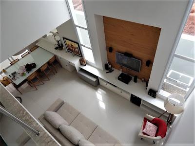 A visão, a partir do mezanino que leva às suítes do pavimento superior, revela a integração da marcenaria com a arquitetura das salas de estar e jantar.