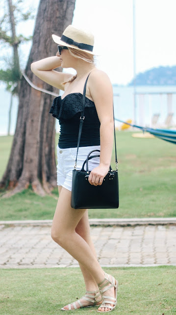 Fashion and Travel Blogger GlobalFashionGal (Brianna Degaston) wearing a black Kate Spade Tote at a resort in Bintan Island, Indonesia.