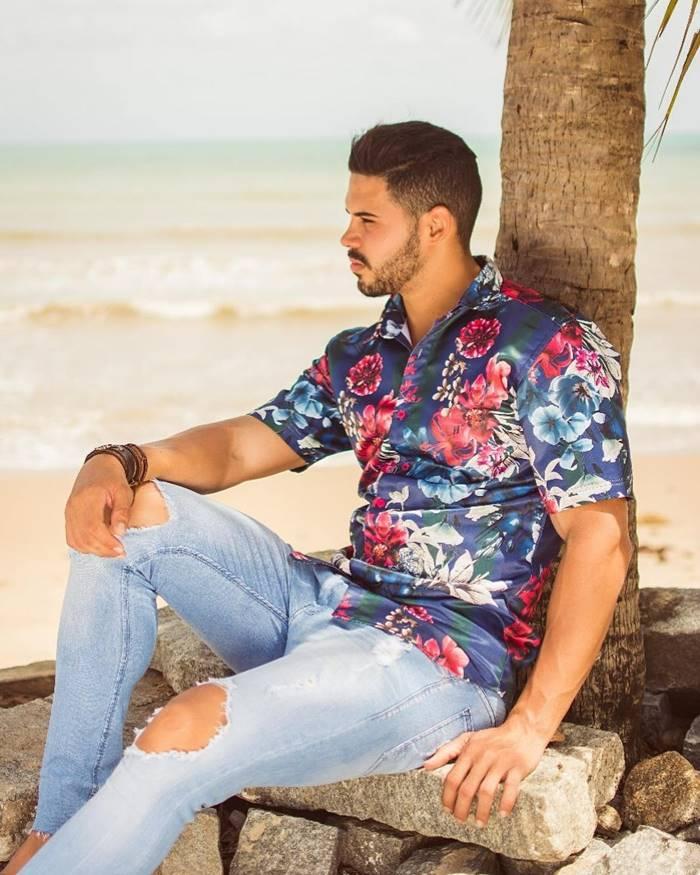 Homem com camisa floral masculina e calça com rasgo no joelho sentado na praia