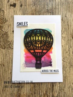 A white card showing a die-cut black hot air balloon flying over a water-coloured rainbow background with the words 'smiles across the miles'