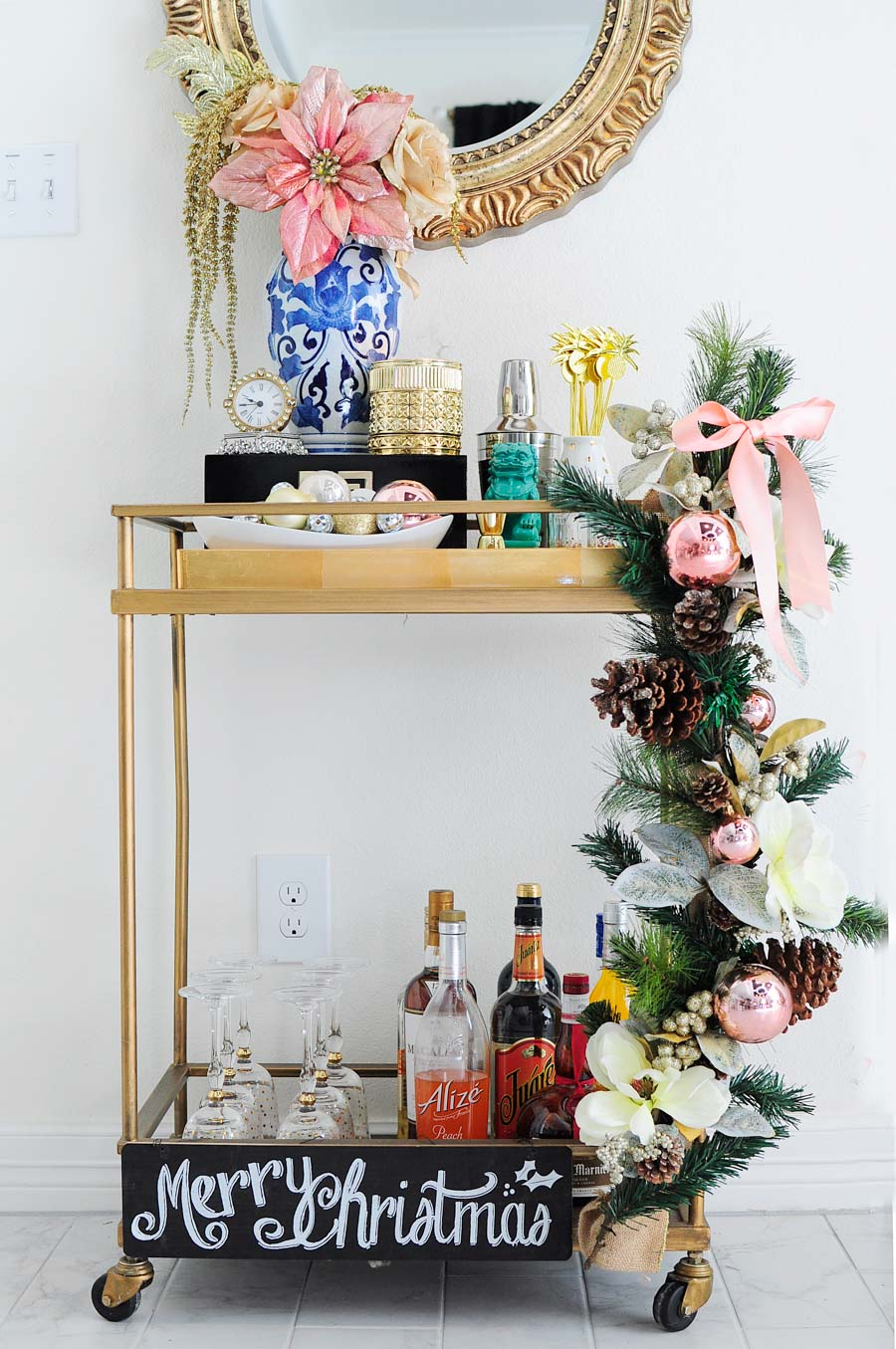 A gorgeous, eclectic bar cart decorated with blush, silver, gold and white accents, a ginger jar vase, foo dog and more. The gold mirror above the cart is perfection.