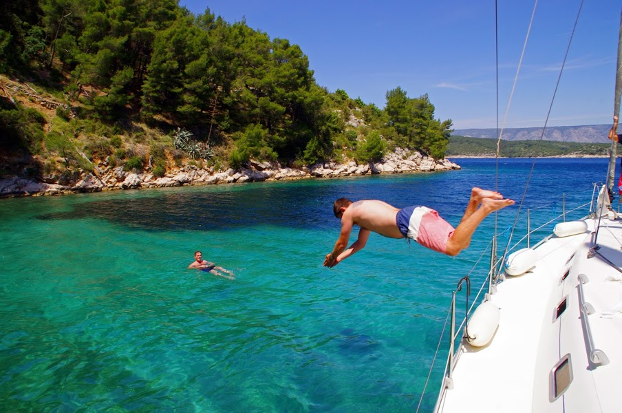 Male jumping off sailing boat in Croatia