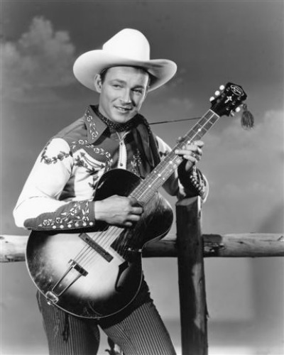 Fifties Cowboy Roy Rogers standing at post railings holding guitar