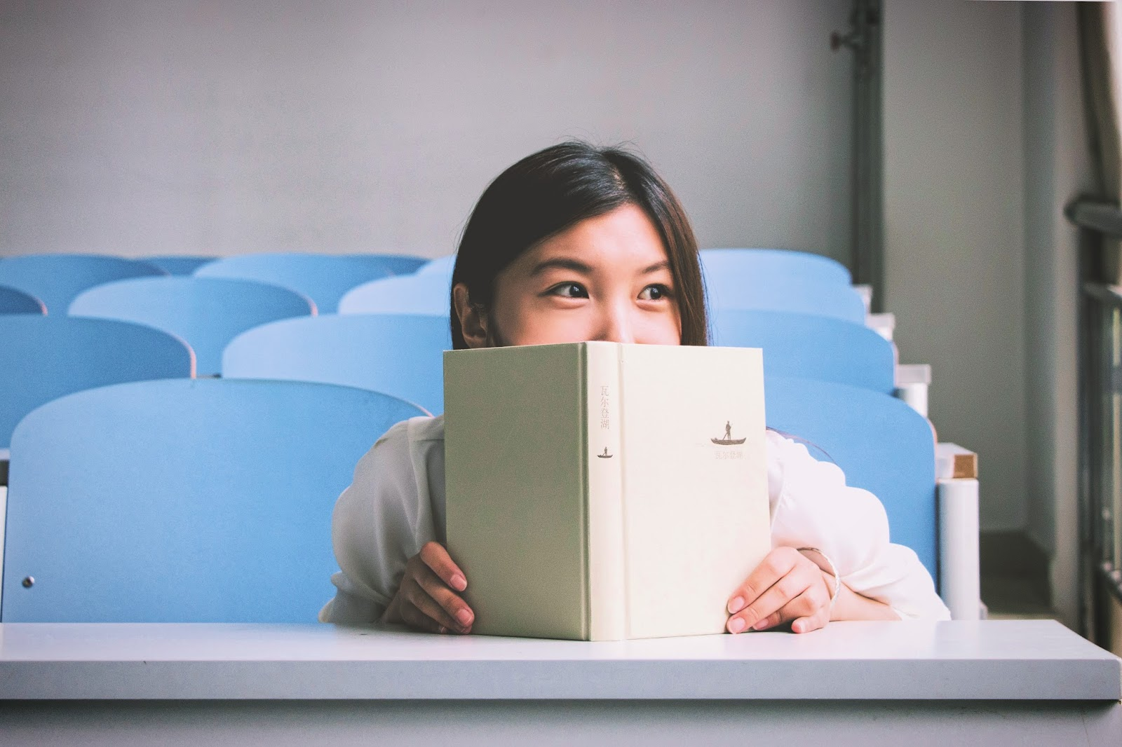Smiling girl hiding behind a book in a lecture theatre with blue chairs