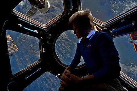Astronaut Peggy Whitson enjoys the view out the observation window on the ISS (Source: NASA)