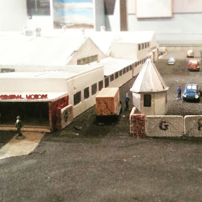 Model of the entrance to a factory complex. On the veranda to the left is a sign saying 'General Motors' and a truck is going through the gate.