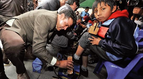 Alcalde Luis Revilla lustrando los calzados de un niño trabajador