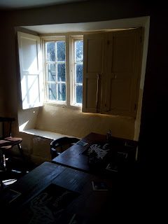View looking towards window with dark old tables and wooden shutters on the window.