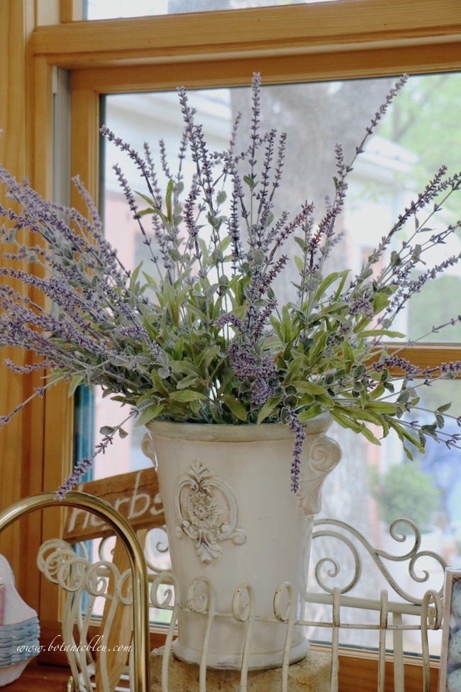 Faux lavender stems in a French style ceramic pot look realistic in garden shed