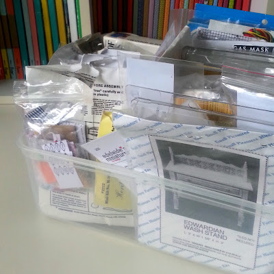 Plastic box full of kits for one-twelfth scale modern miniatures.