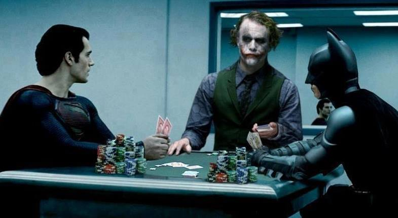 Henry Cavill as Superman, Christian Bale as Batman, and Heath Ledger as Joker seated at table in police interrogation room with cards and poker chips