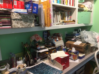 Workbench covered with art supplies, papers, fake flowers, boxes, and more.