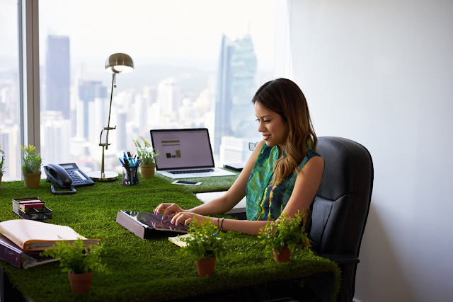 environmentally conscious woman typing at desk covered with grass