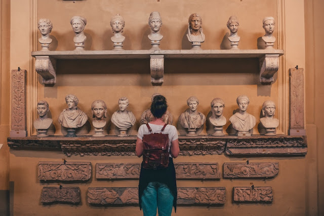 A tourist looking at two shelves full of marble busts