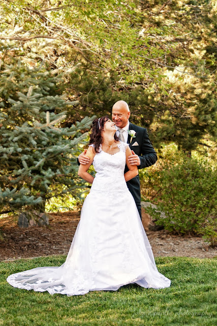 A Bride and Groom smile and look lovingly towards one another for their formal wedding photography pose