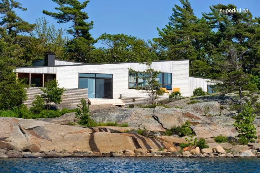 Frente de la moderna cabaña canadiense próxima al borde de la isla