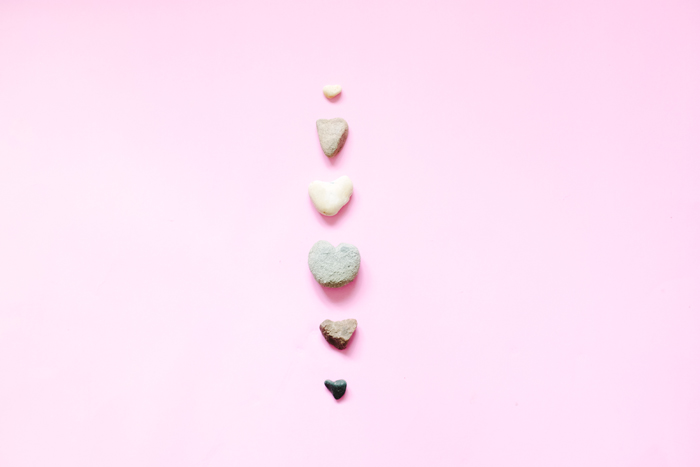 heart rocks on pink paper