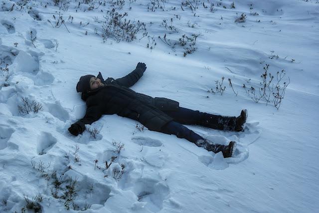 Lud deitada na neve em Ivalo, Finlândia