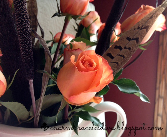 Fall flower arrangement with orange roses and feathers