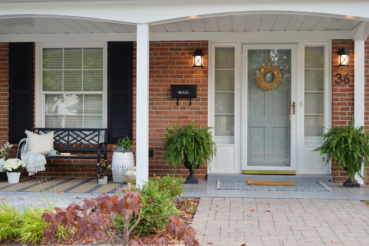 fresh traditional front porch decor with sitting bench and striped Annie Selke rug