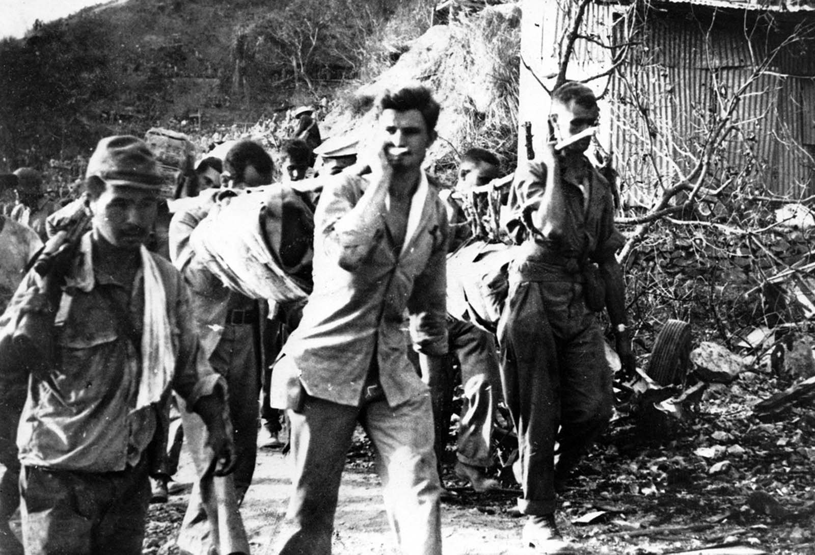 American prisoners of war carry their wounded and sick during the Bataan Death March in April of 1942. This photo was taken from the Japanese during their three year occupation of the Philippines.
