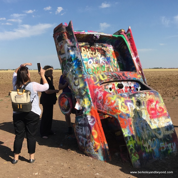 visitor taking a picture at Cadillac Ranch in Amarillo, Texas