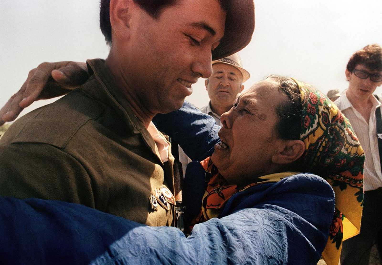 An emotional mother embraces her son, a Soviet soldier who has just crossed the Soviet-Afghan border in Termez, during the withdrawal of Soviet army from Afghanistan, on May 21, 1988.