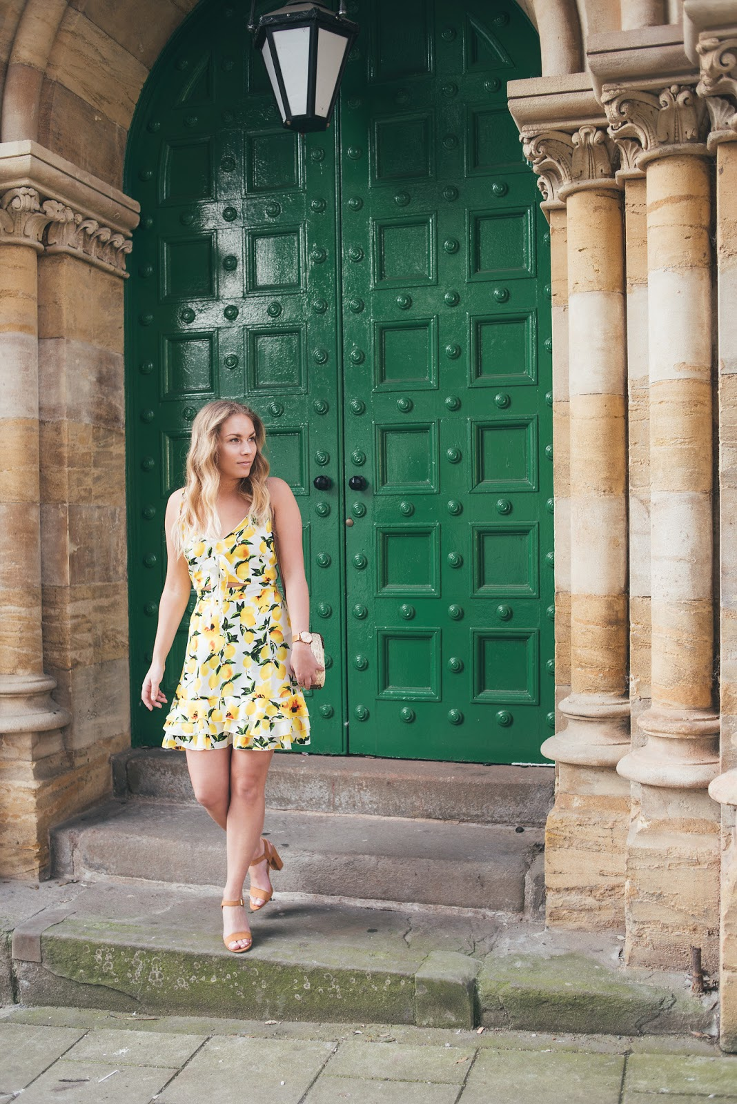Rachel Emily in Lemon Print Dress leaving building with large ornate green door and stone columns either side