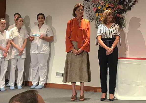 Princess Caroline of Hanover wore Michael Kors silk pussy bow blouse in coral and Miu Miu midi skirt