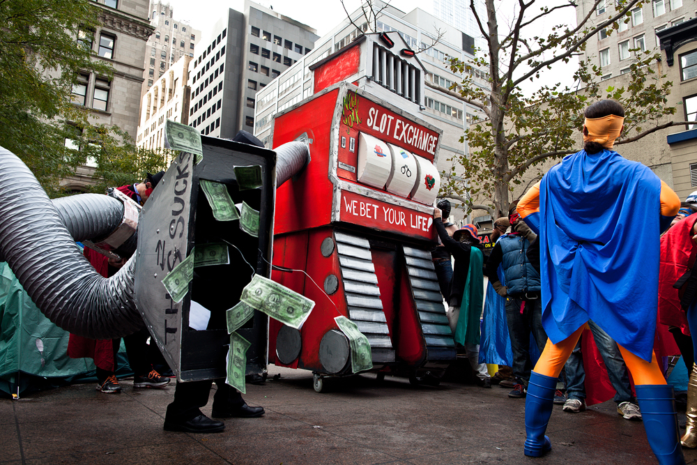 "The Slotbot 3000, a 16-foot-tall robotic representation of the New York Stock Exchange, squares off against Unemployed Man in a ""Superheroes versus Economic Supervillains"" event Monday in New York's Zucotti Park."
