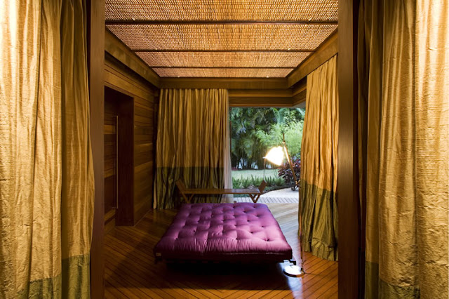 Picture of the massage room with purple bed and golden curtains