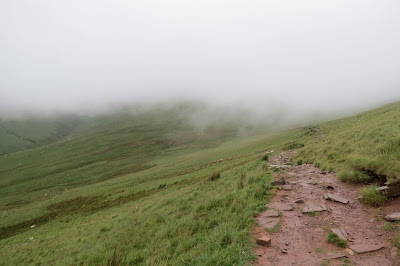 A stone laid path and grass-covered hillside below a layer of cloud.